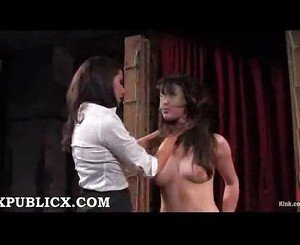 Bound brunette in wooden device
