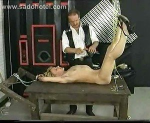 Hot slave with lying on table gets metal clamps removed from